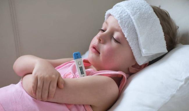 Đắp khăn ấm lên trán của trẻ để làm dịu cơn sốt.
